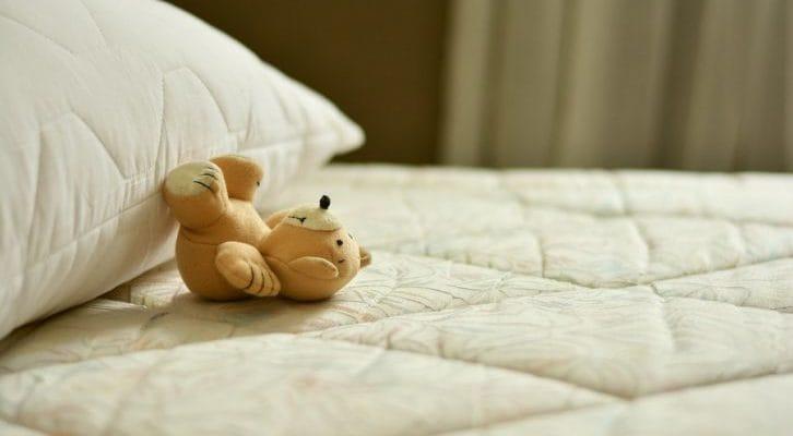 白いベッドにクマのぬいぐるみが置いてある写真
