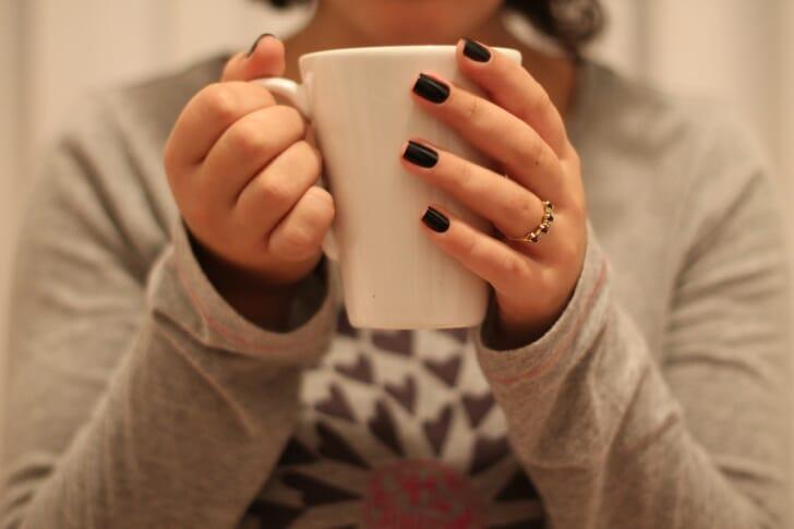 温かい飲み物を持っている女性の写真