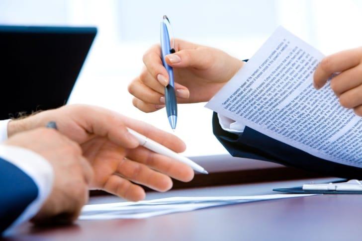 多機能ペンで資料を確認しているビジネスマンの写真