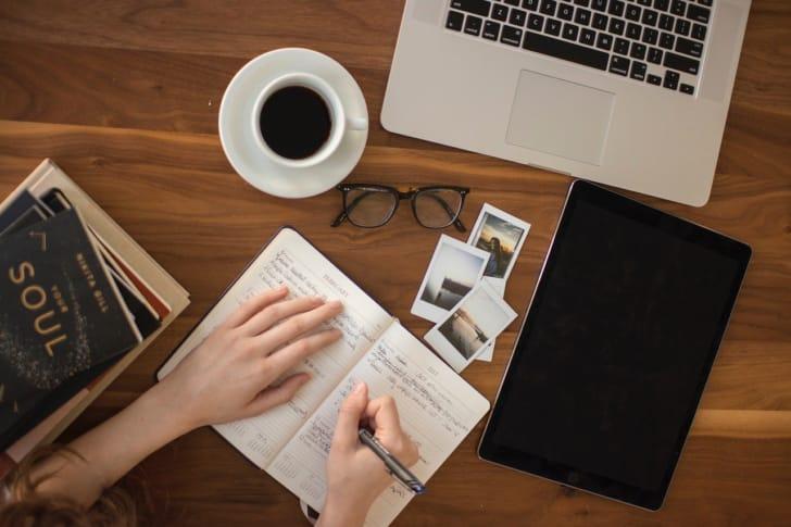 手帳にペンで文字を書いている人の写真