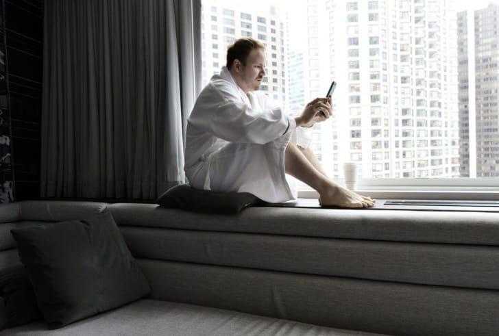 バスローブで窓辺に座る男性の写真