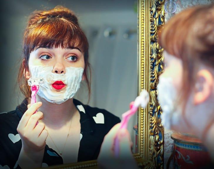フェイスゾーンをシェーバーでお手入れしている女性の写真