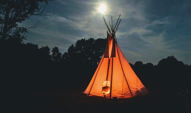 夜のキャンプ場に光るワンポールテントの写真